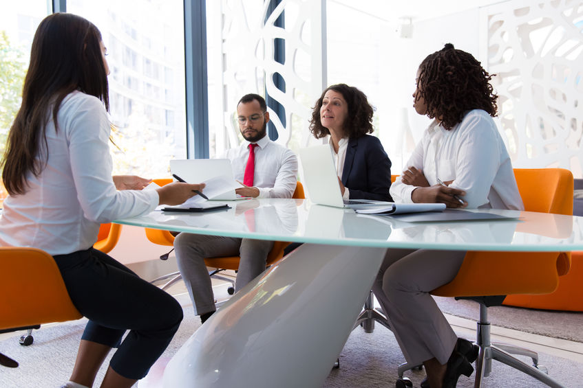 Business leader interviewing job candidate. Business man and women sitting at conference table, using laptops and talking. Discussion agreement concept