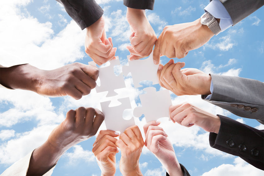 Directly below shot of multiethnic business people assembling jigsaw puzzle against sky